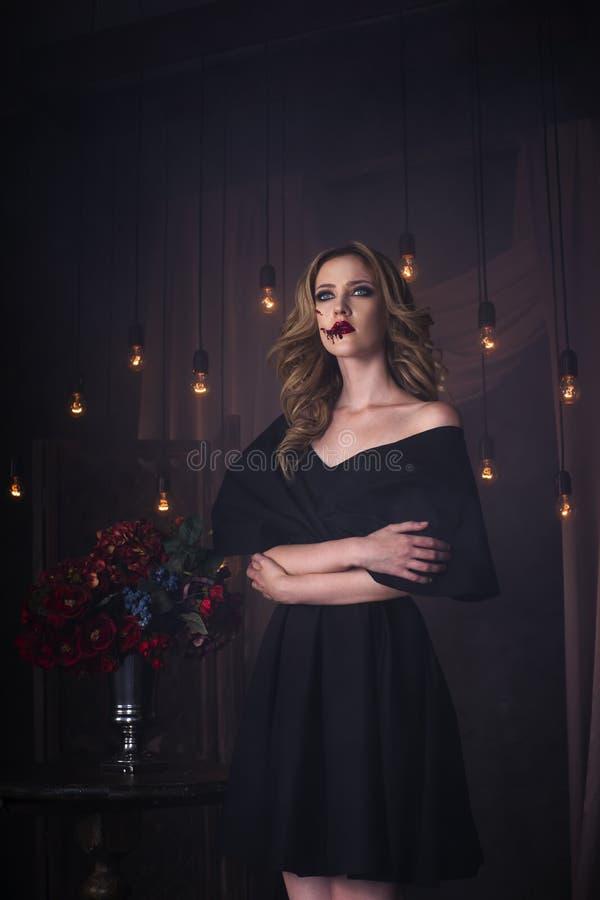 La mujer rubia joven hermosa en vestido negro con Halloween compone y arte sangriento de la cara fotografía de archivo