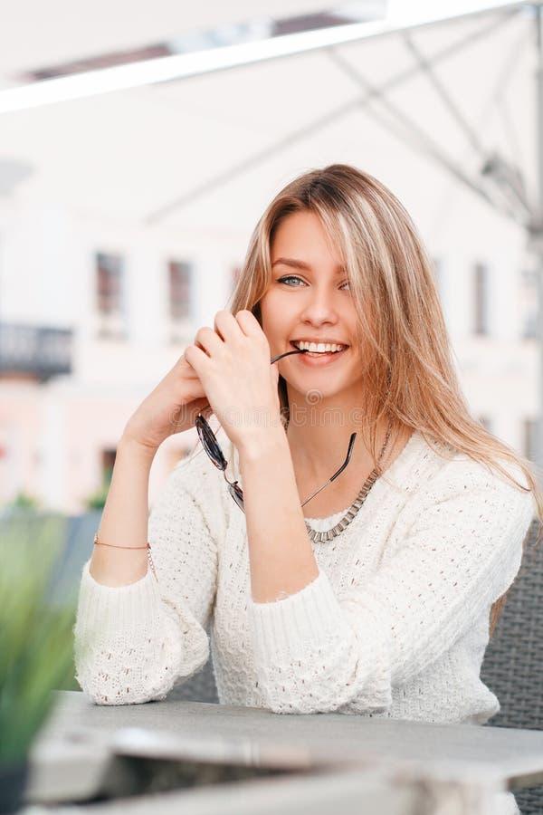 La mujer rubia joven linda divertida en un suéter blanco hecho punto vintage se está sentando en una tabla en un café de la calle foto de archivo