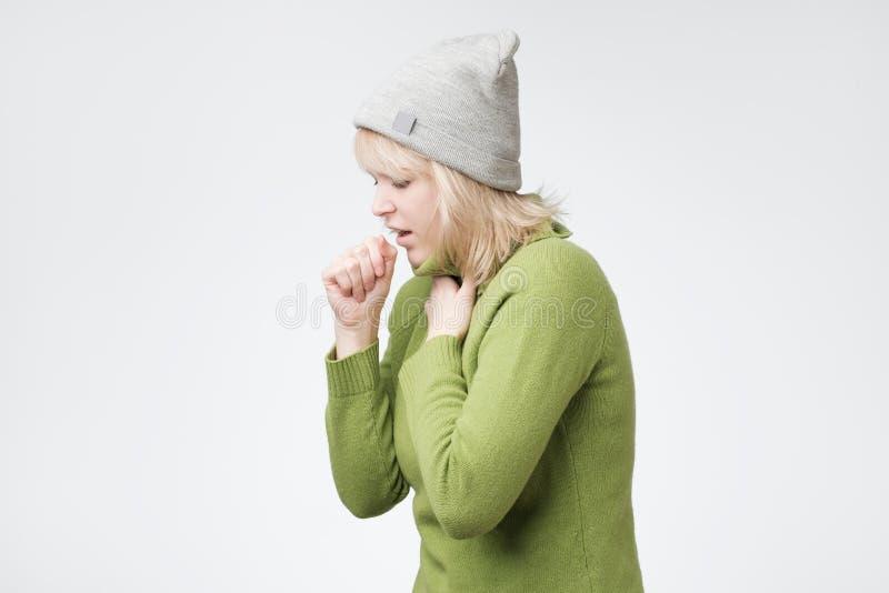 La mujer rubia joven malsana que tose mucho, sufriendo con tos, tiene un dolor de pecho fotos de archivo