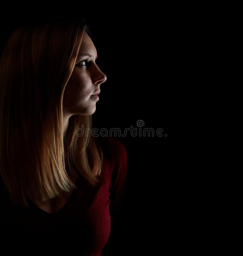La mujer rubia joven mira cuidadosamente a un lado imagenes de archivo