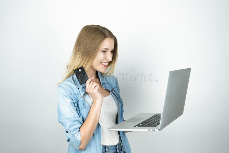 La mujer rubia joven parece feliz sosteniendo su tarjeta de banco en un mano y ordenador portátil en otro, en línea haciendo comp fotografía de archivo