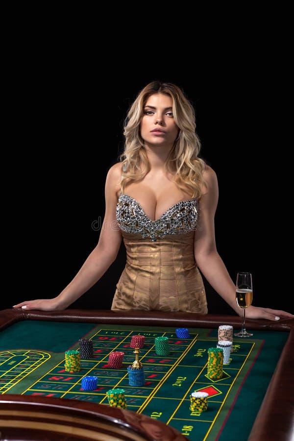 La mujer rubia joven que lleva el vestido brillante atractivo hermoso está jugando la ruleta en el casino foto de archivo libre de regalías