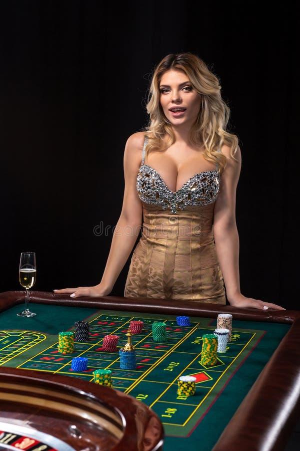 La mujer rubia joven que lleva el vestido brillante atractivo hermoso está jugando la ruleta en el casino foto de archivo