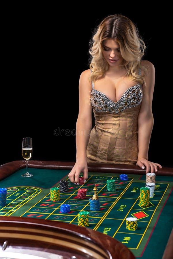 La mujer rubia joven que lleva el vestido brillante atractivo hermoso está jugando la ruleta en el casino fotos de archivo libres de regalías