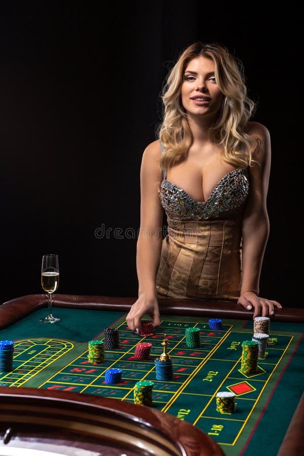La mujer rubia joven que lleva el vestido brillante atractivo hermoso está jugando la ruleta en el casino fotografía de archivo libre de regalías