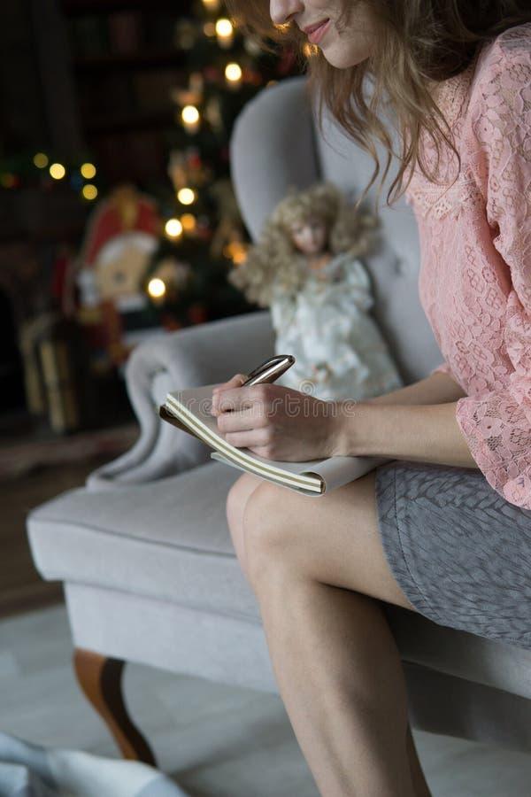 La mujer rubia joven se sienta en un sofá gris en una blusa rosada y escribe con su mano izquierda con una pluma en un cuaderno a fotos de archivo libres de regalías