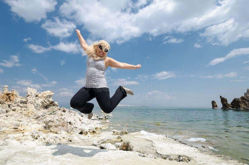 La mujer rubia salta en el mono lago en California, concepto para la libertad, ganador, éxito foto de archivo libre de regalías