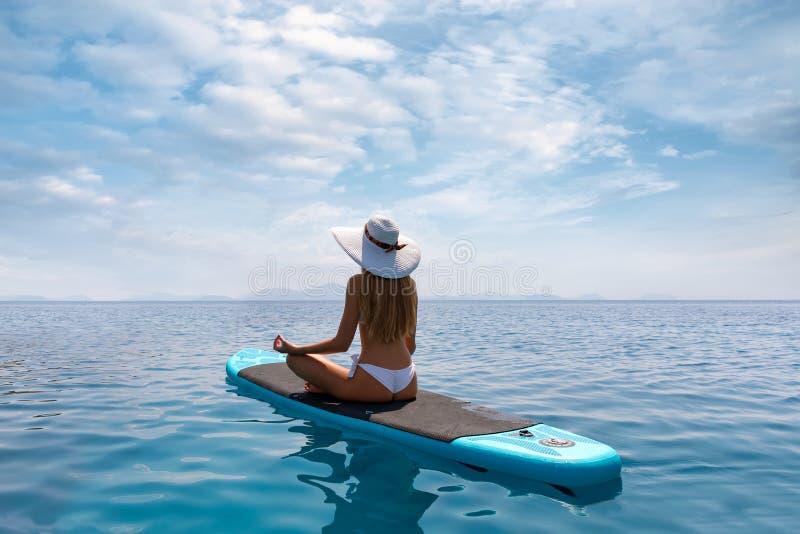 La mujer rubia se relaja en una posición de la yoga respecto a un soporte encima del SORBO del tablero de paleta fotos de archivo