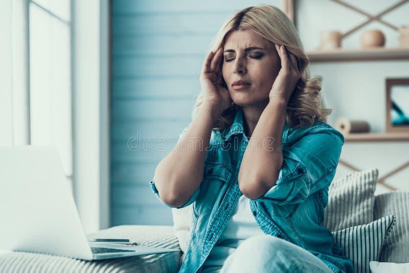 La mujer rubia tiene dolor de cabeza en el trabajo con el ordenador portátil fotografía de archivo