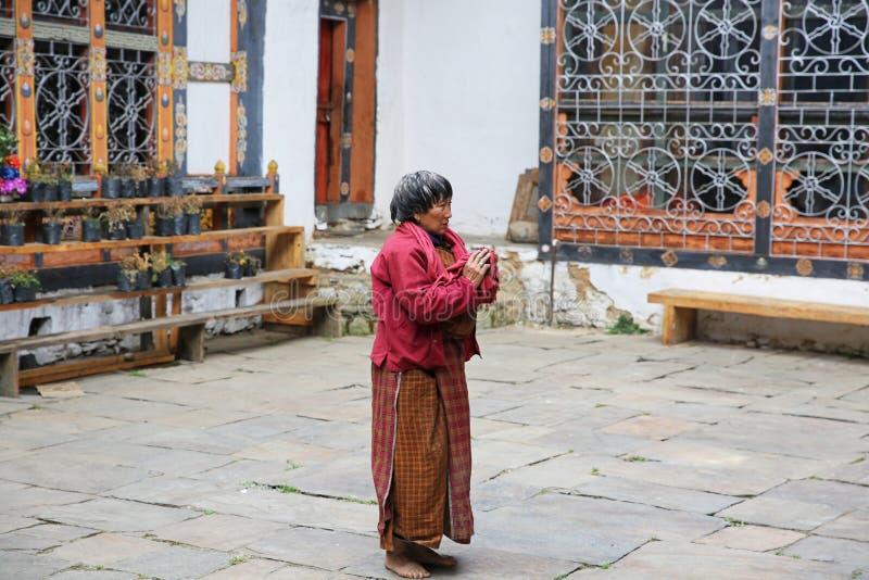 La mujer ruega en el templo budista, Bhután fotografía de archivo