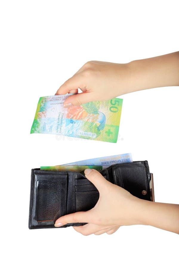 La mujer saca francos suizos de su monedero imagenes de archivo
