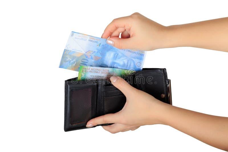 La mujer saca francos suizos de su monedero foto de archivo libre de regalías
