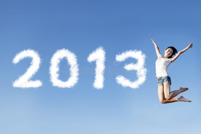 La mujer salta acogiendo con satisfacción el Año Nuevo 2013 imagen de archivo
