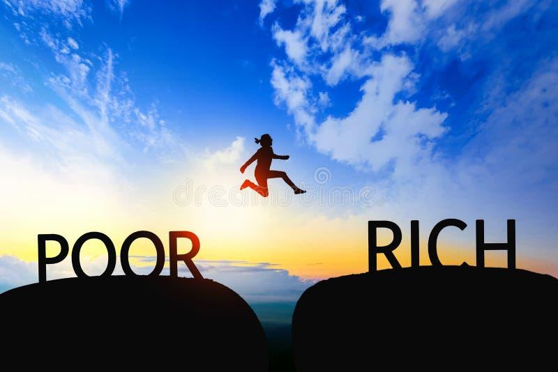 La mujer salta con el hueco entre los POBRES a los RICOS en puesta del sol imágenes de archivo libres de regalías