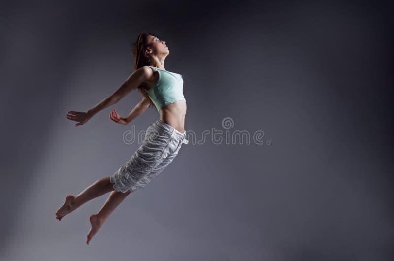 La mujer salta Danza de la muchacha de la belleza en fondo gris fotos de archivo
