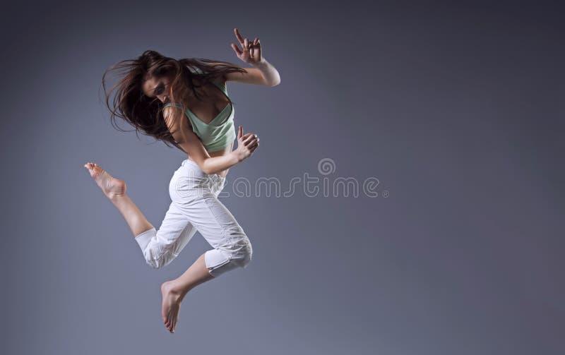 La mujer salta Danza de la muchacha de la belleza en fondo gris imagen de archivo