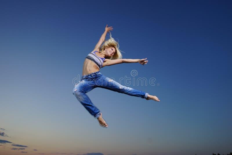 La mujer salta en la noche imagen de archivo libre de regalías