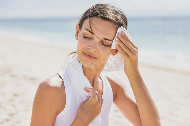 La mujer sana limpia hacia fuera su sudor con la toalla después de entrenamiento foto de archivo