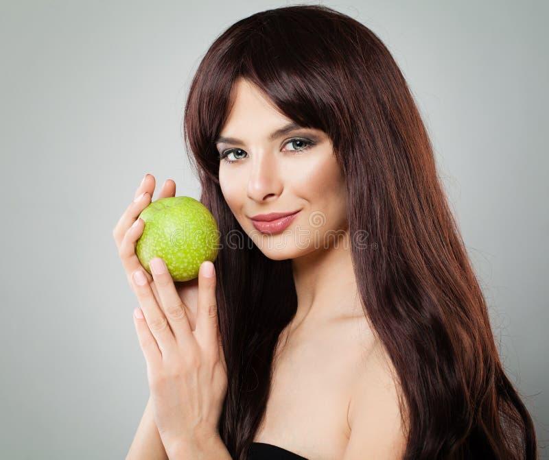 La mujer sana que sonríe y que sostiene Apple verde da fruto foto de archivo