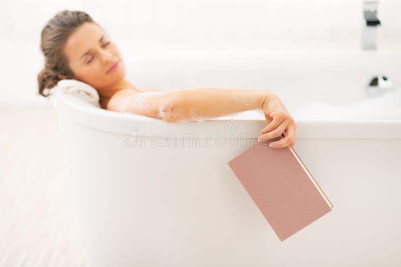 La mujer se cae dormido mientras que libro de lectura en bañera imágenes de archivo libres de regalías