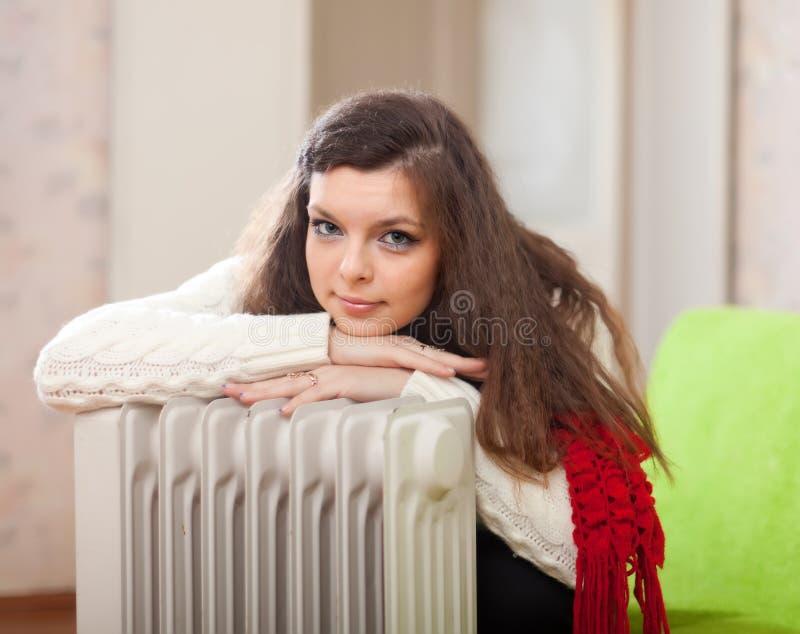 La mujer se calienta cerca del calentador imagen de archivo