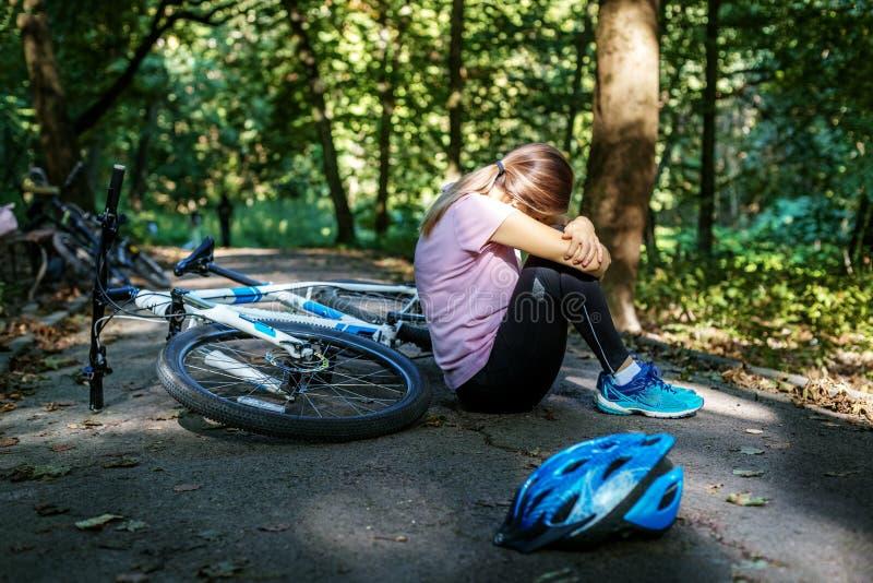 La mujer se cayó de la bici trauma El concepto de ciclo y fotografía de archivo libre de regalías