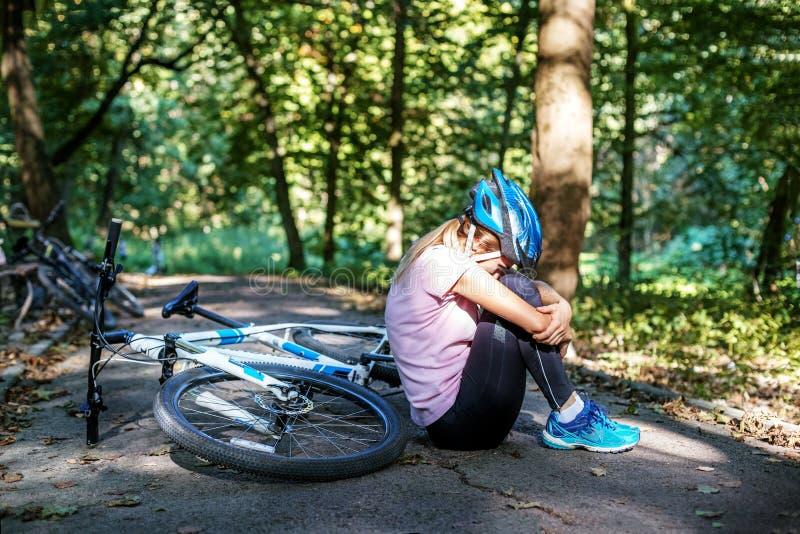La mujer se cayó de una bicicleta en un casco trauma El concepto o imagenes de archivo