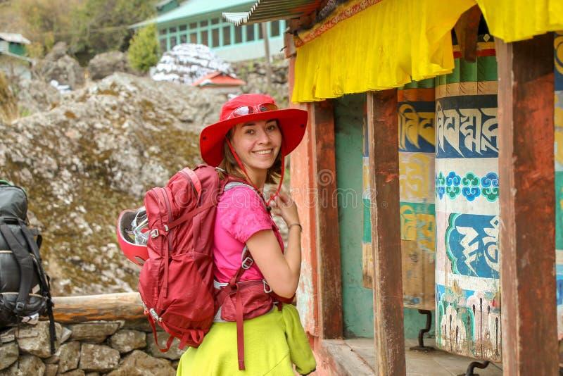 La mujer se coloca al lado de las ruedas de un rezo coloridas adentro Nepal foto de archivo