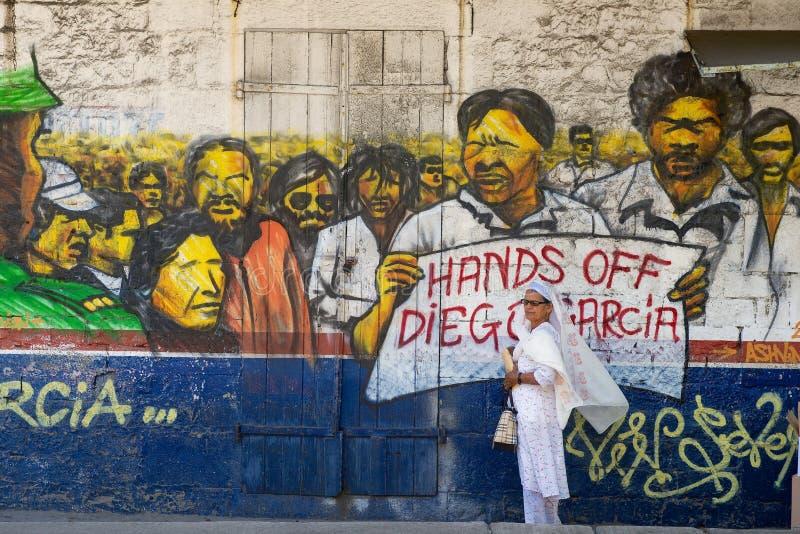 La mujer se coloca en la calle con el cartel político 'manos de Diego Garcia 'pintado en la pared en Ville Noire, isla de Maurici foto de archivo