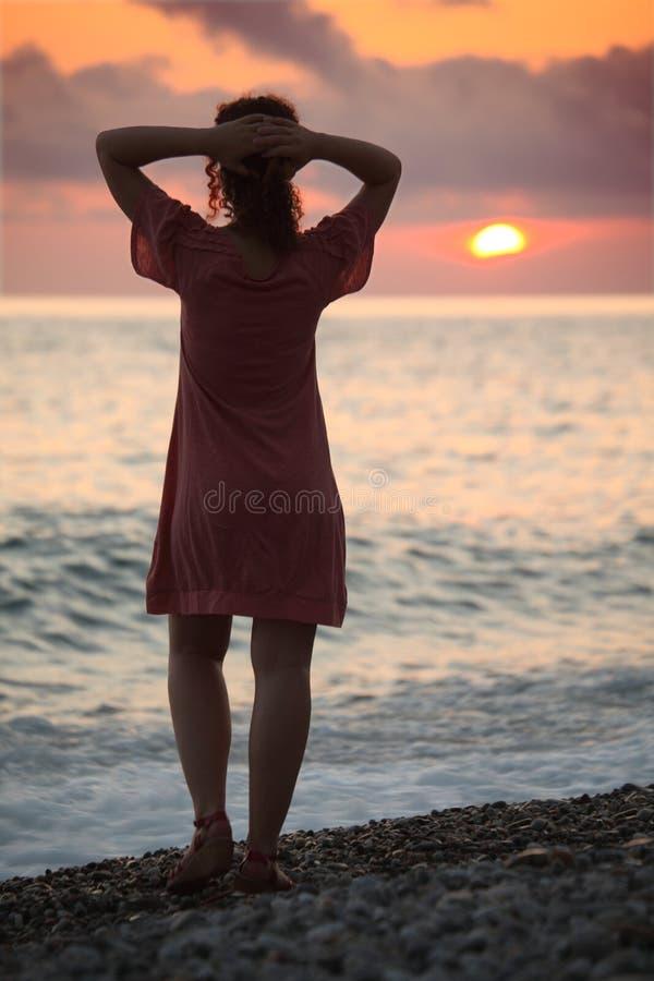 La mujer se coloca en la costa en la puesta del sol, visión trasera fotografía de archivo libre de regalías