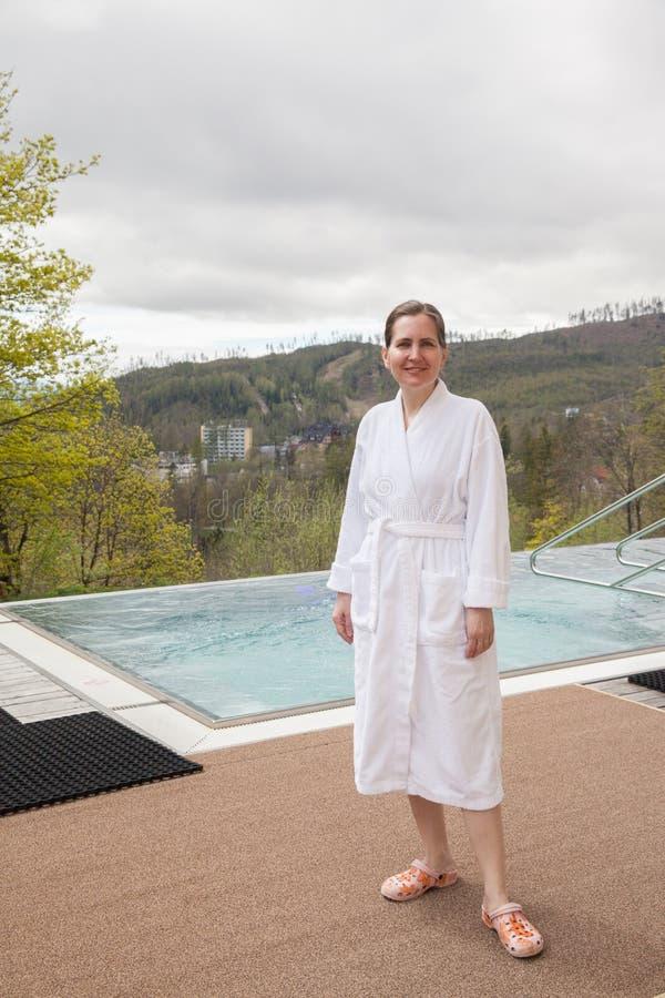 La mujer se coloca en la piscina exterior fotos de archivo libres de regalías