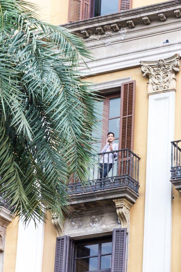 La mujer se colocaba en balcón en el teléfono móvil fotografía de archivo libre de regalías