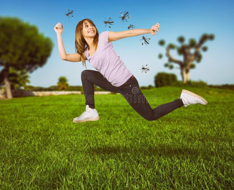 La mujer se defiende del ataque de los mosquitos que corren rápidamente foto de archivo