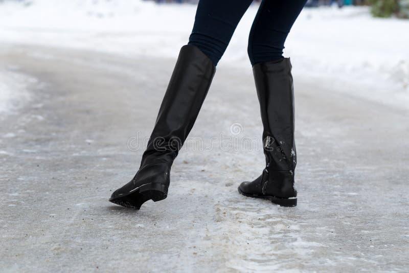 La mujer se desliza en el camino resbaladizo cubierto con hielo Concepto de riesgo de lesión en invierno foto de archivo