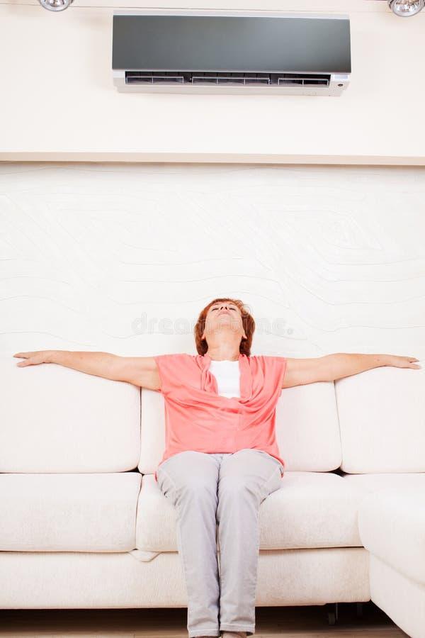 La mujer se escapa del calor debajo del acondicionador de aire fotografía de archivo libre de regalías