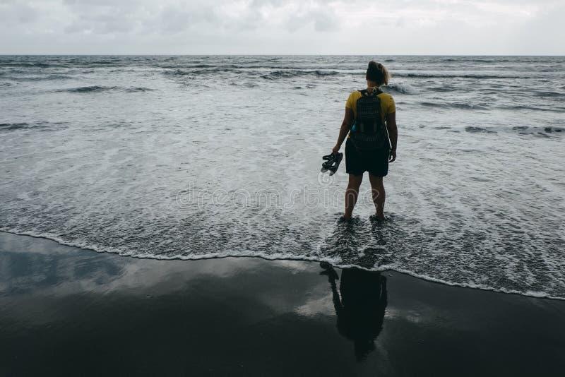 La mujer se está colocando en la playa y está mirando al mar en la distancia fotos de archivo libres de regalías