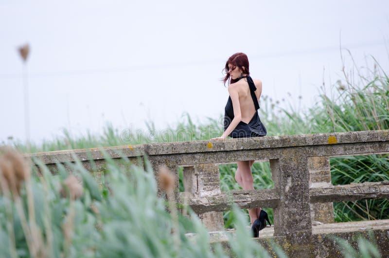 La mujer se está colocando en un puente viejo del cemento imágenes de archivo libres de regalías