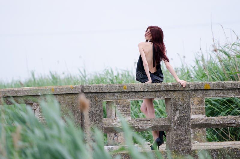 La mujer se está colocando en un puente viejo del cemento fotos de archivo