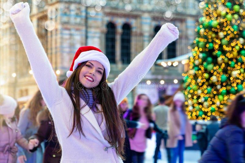 La mujer se está divirtiendo en una pista de hielo de la Navidad imagen de archivo libre de regalías