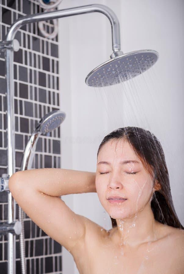 La mujer se está lavando el pelo y la cara por la ducha de lluvia fotos de archivo