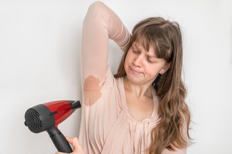 La mujer se está secando el axila sudante con el secador de pelo imagen de archivo