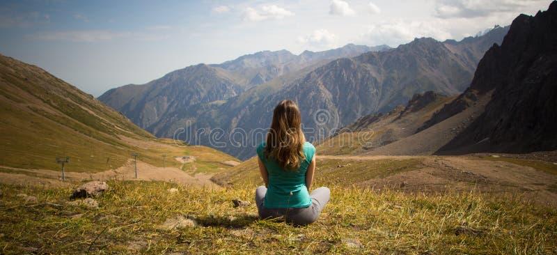 La mujer se está sentando en estilo de la yoga y está mirando en la distancia fotografía de archivo