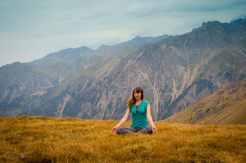 La mujer se está sentando en estilo de la yoga y está mirando en la distancia fotos de archivo