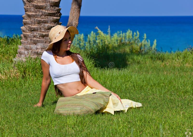 La mujer se está sentando en hierba verde cerca del mar imagenes de archivo