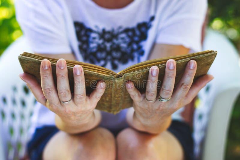 La mujer se está sentando en silla y está leyendo un libro viejo imágenes de archivo libres de regalías