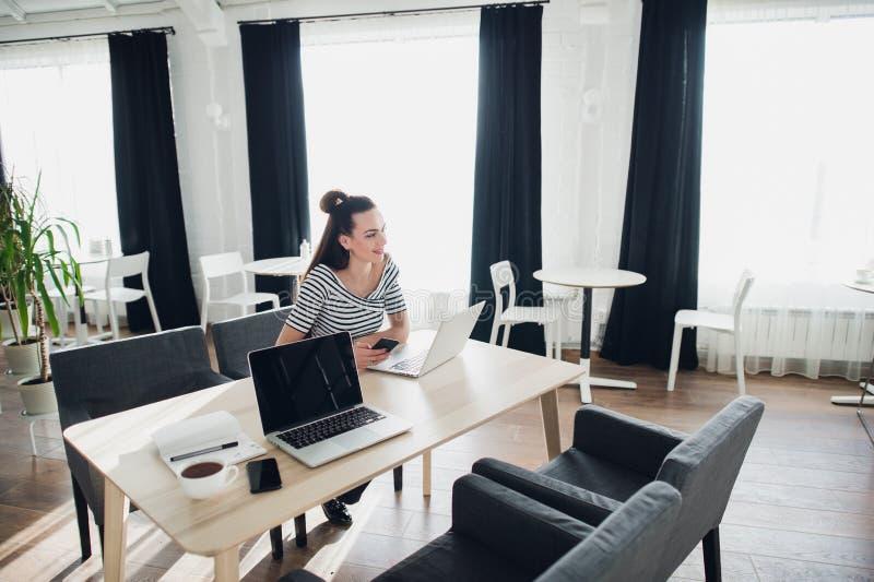 La mujer se está sentando en un café y está trabajando en su ordenador portátil y smartphone mientras que feliz mira lejos que in fotografía de archivo libre de regalías