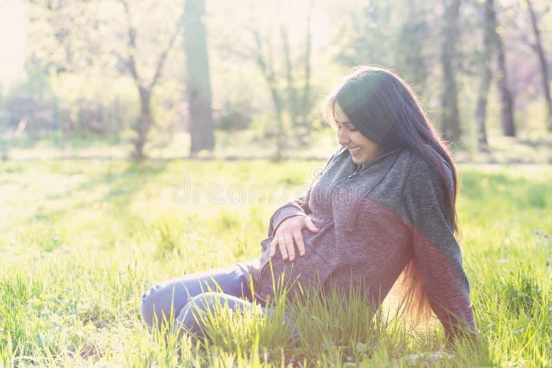 La mujer se está sentando en un prado imagen de archivo libre de regalías