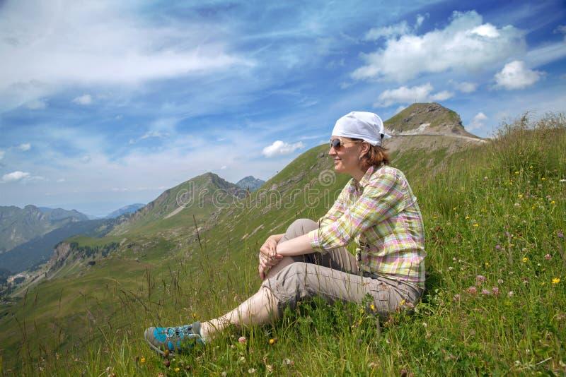 La mujer se está sentando en una montaña imagen de archivo