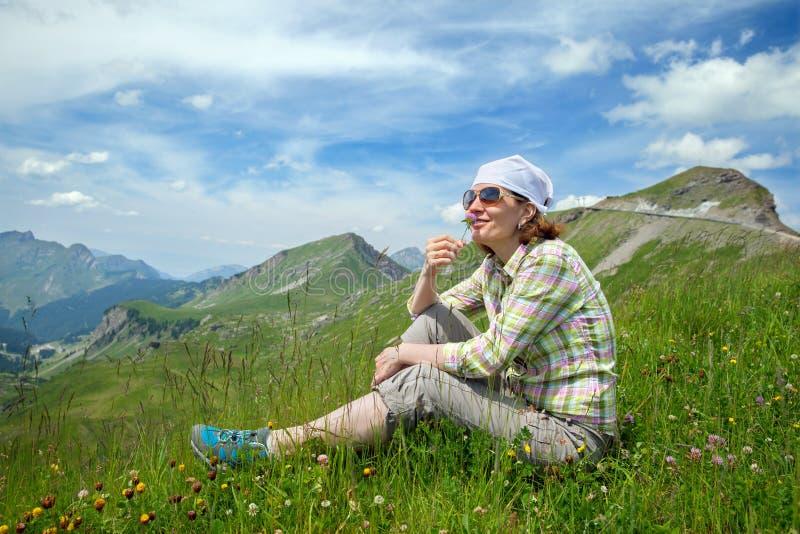 La mujer se está sentando en una montaña con la flor del trébol fotografía de archivo