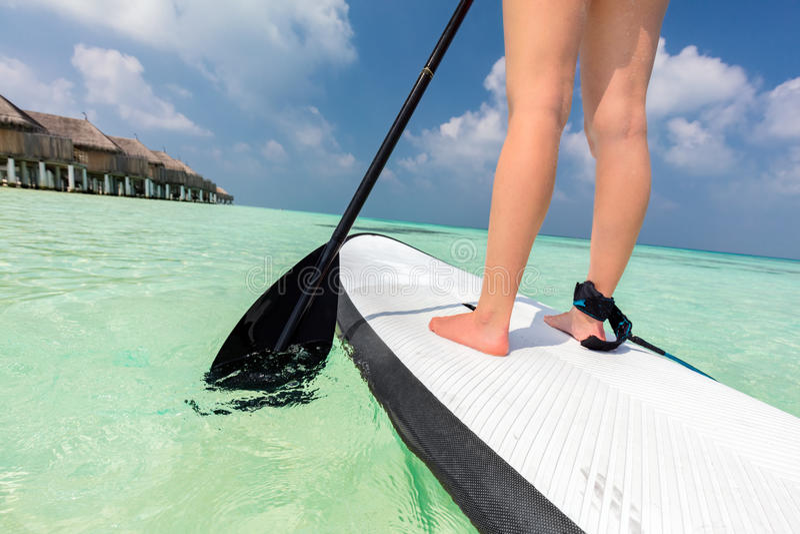 La mujer se levanta el embarque de la paleta en el océano en Maldivas foto de archivo libre de regalías